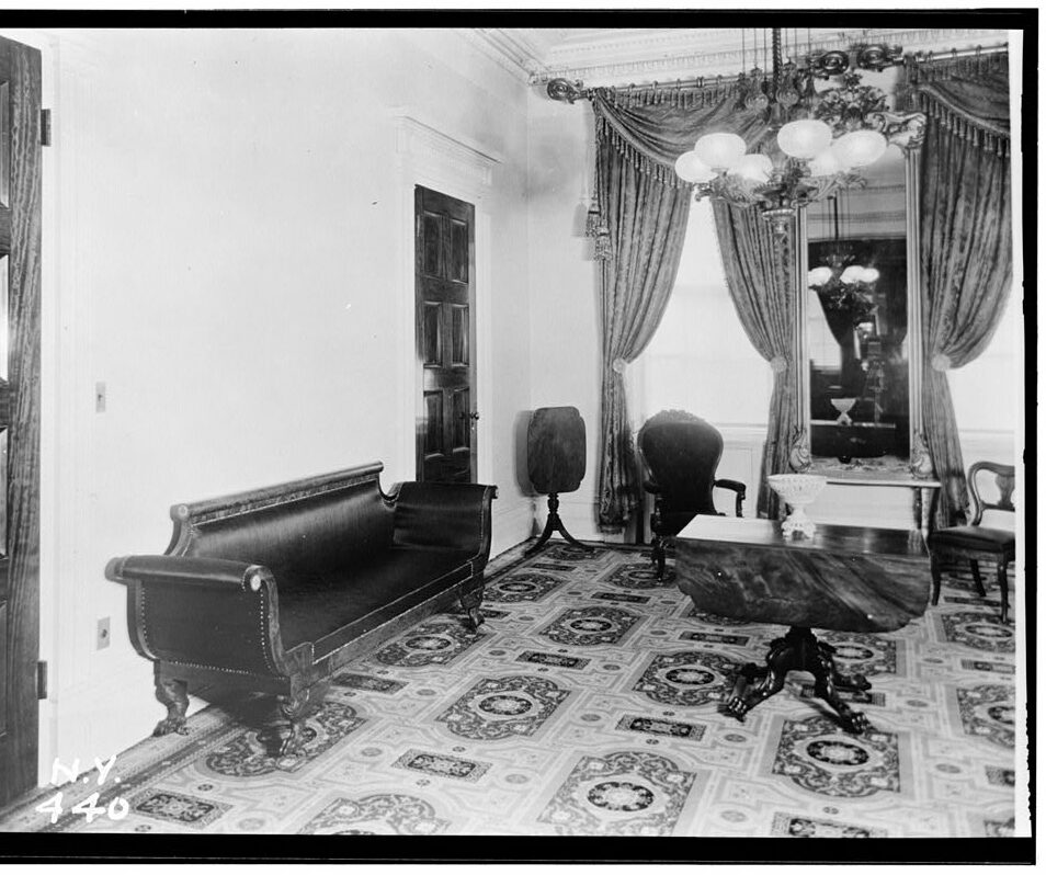 1936 black and white photograph of the Museum's front parlor. An empire-style black horsehair sofa sits along the east wall between two mahogany doors; on the adjacent wall are two large windows with elaborate silk drapery.